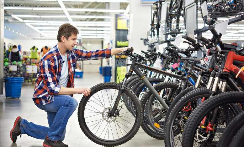 Père avec un adolescent demandant de l'aide à une vendeuse positive pour un magasin de vélo de sport